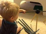 Two year old using his fine motor skills to put the pole into the connector